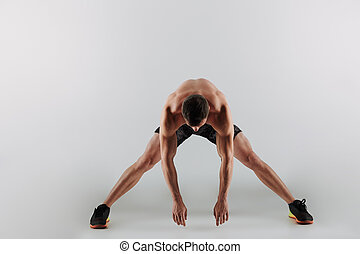 Concentrated young sportsman make stretching exercises -...