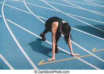 Concentrated young sportswoman in starting position on running track stadium