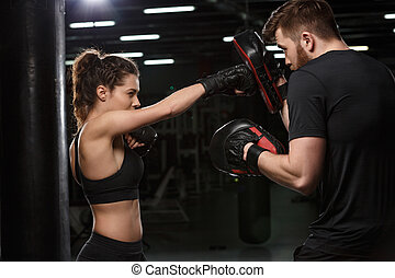 Concentrated young strong sports lady boxer make exercises
