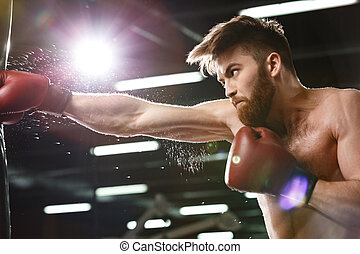 Concentrated young strong sports man boxer