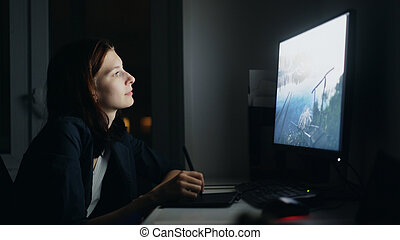 Concentrated young woman designer working at home at night using computer and graphics tablet to finish job