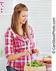 Concentrated young woman preparing a salad