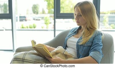 Concentrated young woman reading book - Time to relax. Side...