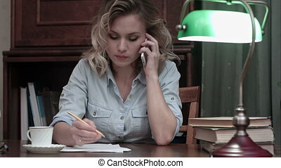 Concentrated young woman talking business on the phone and making notes at her desk