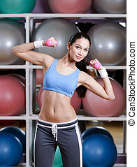 Concentrated young woman training with dumbbells