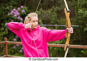 Concentrating blonde practicing archery at the range
