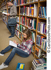 Concentrating student reading book on library floor