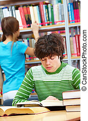 Concentration - Guy reading book while his female classmate...
