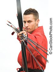 Young archer concentrating and aiming at the camera, focus on face