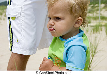concentration - young baby boy plays on the beach with his...