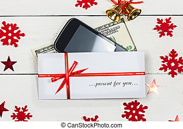 """A stack of banknotes, a smartphone and an envelope with the inscription """"Present for you."""""""