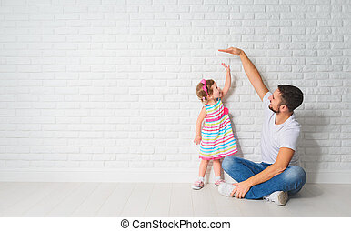 concept. Dad measures the growth of her child daughter at a blank brick wall
