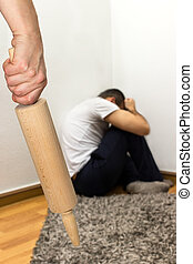Concept domestic abuse - Woman treats a man with a rolling...
