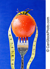 fork with tomato and measure tape