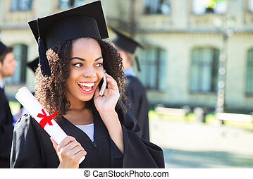 Young Afro American female student dressed in black graduation gown. Campus as a background. Girl smiling, holding diploma and talking on phone