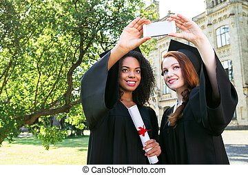 Young female students dressed in black graduation gown. Campus as a background. Girls smiling and making selfie photo on mobile phone