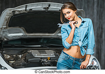 Concept for young sexy female car repair - Photo of young...