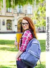 Photo of young female student with backpack, glasses and books. Campus as a background. Girl smiling and looking at camera