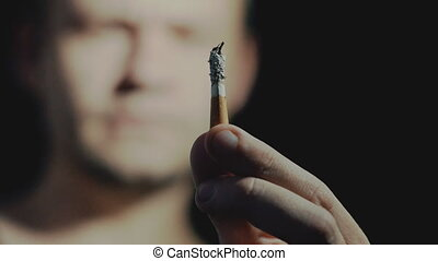 Concept harm of smoking, man holds in his hand a cigarette...