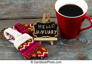 Concept HELLO january message on blackboard with a Cup of coffee and mittens