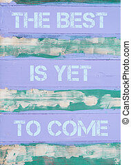 Concept image of THE BEST IS YET TO COME motivational quote written on vintage painted wooden wall