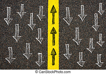 Road marking yellow paint dividing line between arrows going in different directions, Find Your Own Way concept
