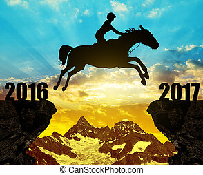 Concept New Year 2017 - The rider on the horse jumping into...