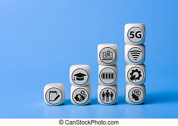 Concept of 5G with icons on wooden cubes. Blue background.