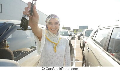 Concept of buying a car. Happy muslim woman holding car key.