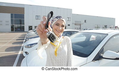 Concept of buying a car. Happy muslim woman holding car key....