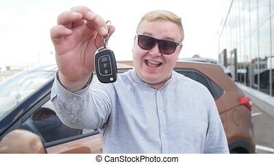Concept of buying and renting a car. Happy man with car keys near the showroom