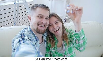 Concept of buying and renting real estate. Happy couple showing keys of new home
