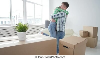 Concept of buying and renting real estate. Lucky young couple embracing in new house