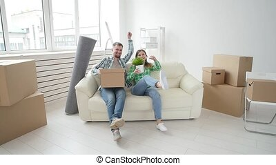 Concept of buying and renting real estate. Young happy family couple bought or rented their first small apartment