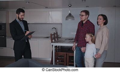 Real estate agent showing new house to family of three...