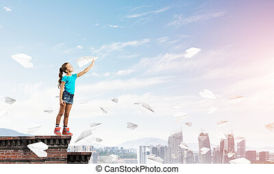 Concept of careless happy childhood with girl dreaming to become pilot