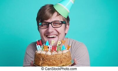 Concept of celebration and fun. Smiling happy crazy young man in party hat holding a birthday cake