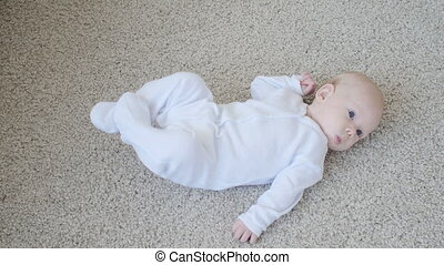 Concept of children and parenthood. Cute Happy Baby is Lying on Carpet