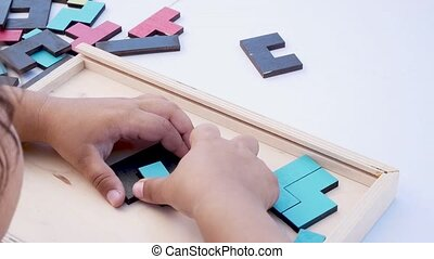 Concept of children's education. Closeup Slow motion. Hand holding piece of wooden block puzzle. wood cube stacking. Concept of complex and smart logical thinking.
