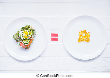 Concept of choice and equality - healthy food or medical pills, top view on the white plates and wooden table. Choice between natural and synthetic way of health care. Alternative medicine.