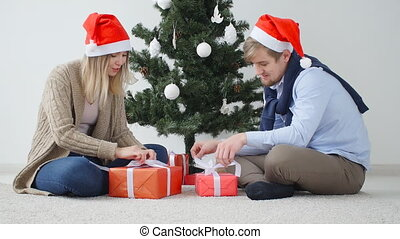Concept of Christmas and happy New Year. Happy young couple opening a Christmas presents