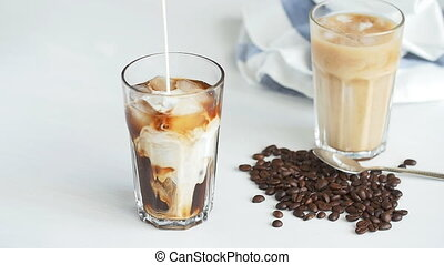 Concept of coffee and cocktails. Cream poured into coffee...