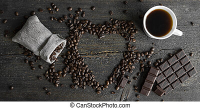 Concept of coffee lover. Coffee beans scattered from a linen bag in a heart shape on a wooden table. Cup of coffee and bar of dark chocolate. Mug of black coffee.