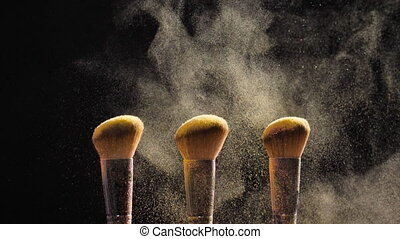 Concept of cosmetics and beauty. Brushes with golden...