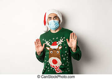Concept of covid-19 and Christmas holidays. Anxious and freak out guy in santa hat with medical mask rejecting something, declining offer, standing over white background
