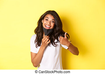 Concept of covid-19, social distancing and lifestyle. Portrait of attractive african-american woman smiling, taking-off face mask and showing thumbs-up, recommend something