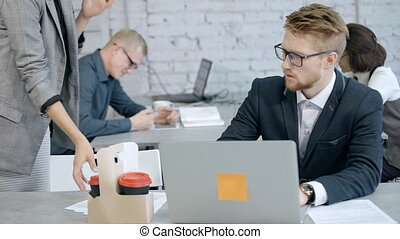 Concept of creative people in business. Qualified and successful businessman using laptop computer and planning new project or strategy online. Adult woman bring coffee to his leadership man