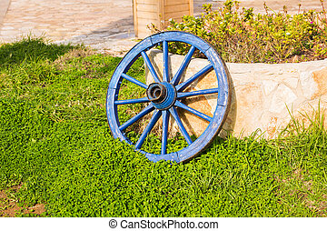 Concept of decor for garden - wooden wheel on a background of green grass