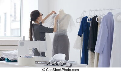 Concept of design and production of clothing. Young seamstress clothes designer working in his studio