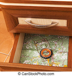 map and compass in open desk drawer